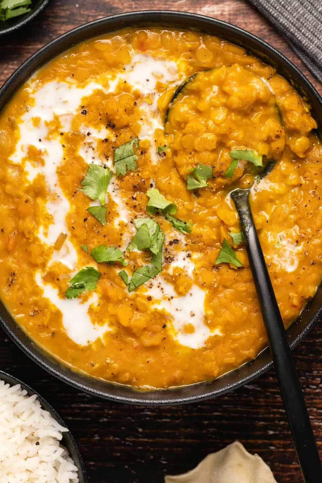 Lentil dal in a black bowl with a spoon.
