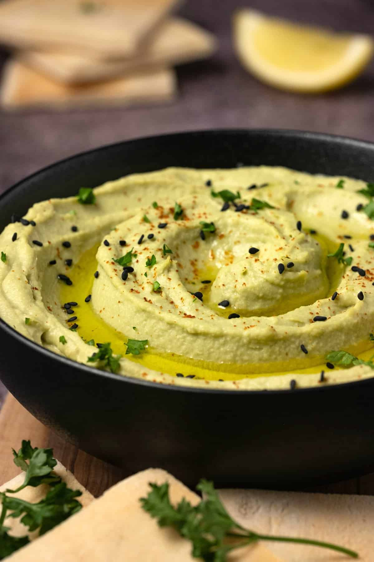 Black bowl of avocado hummus.