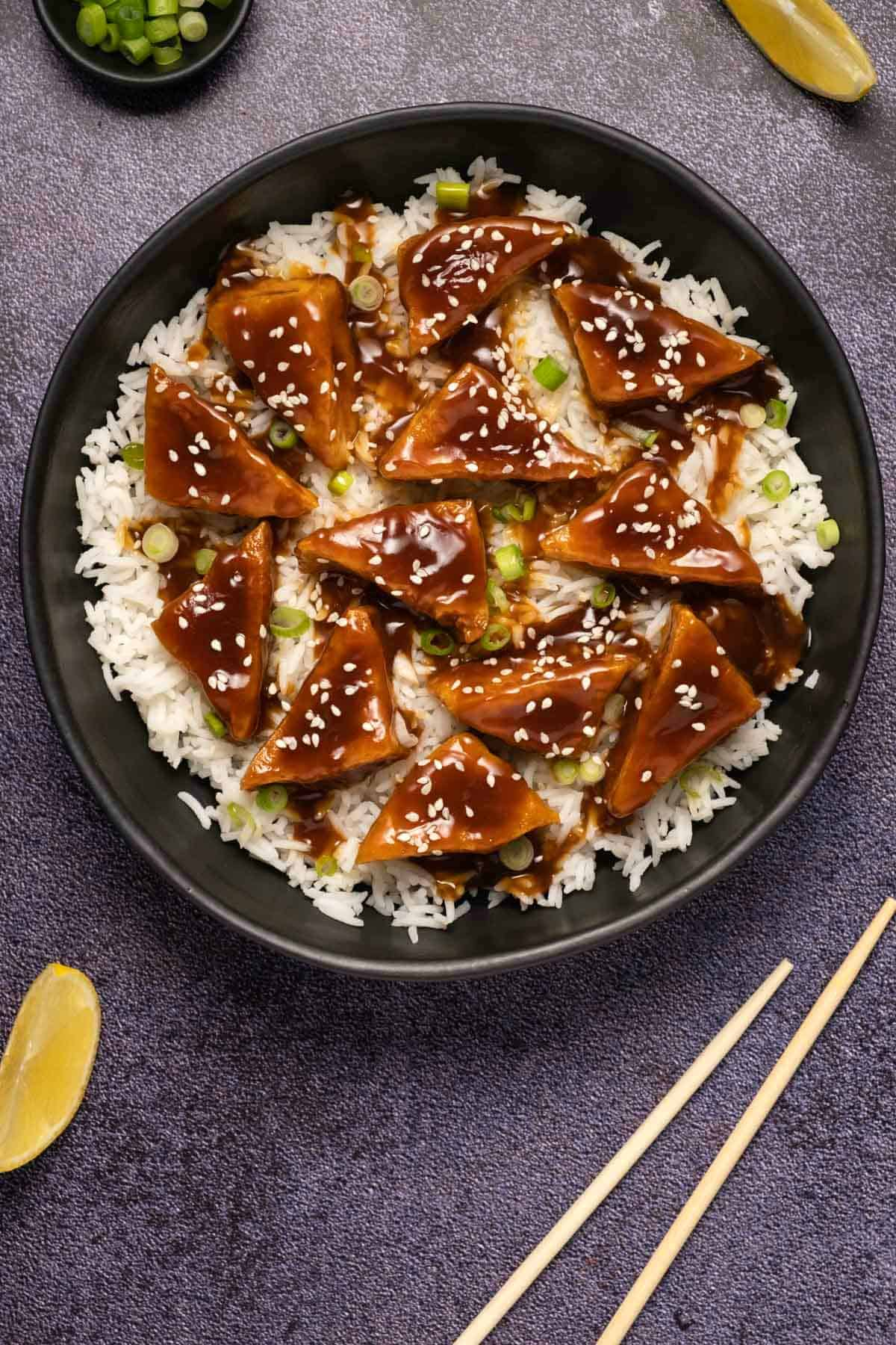 Teriyaki tofu with sesame seeds, chopped spring onions and rice in a black bowl.