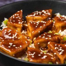 Teriyaki tofu with rice in a black bowl.