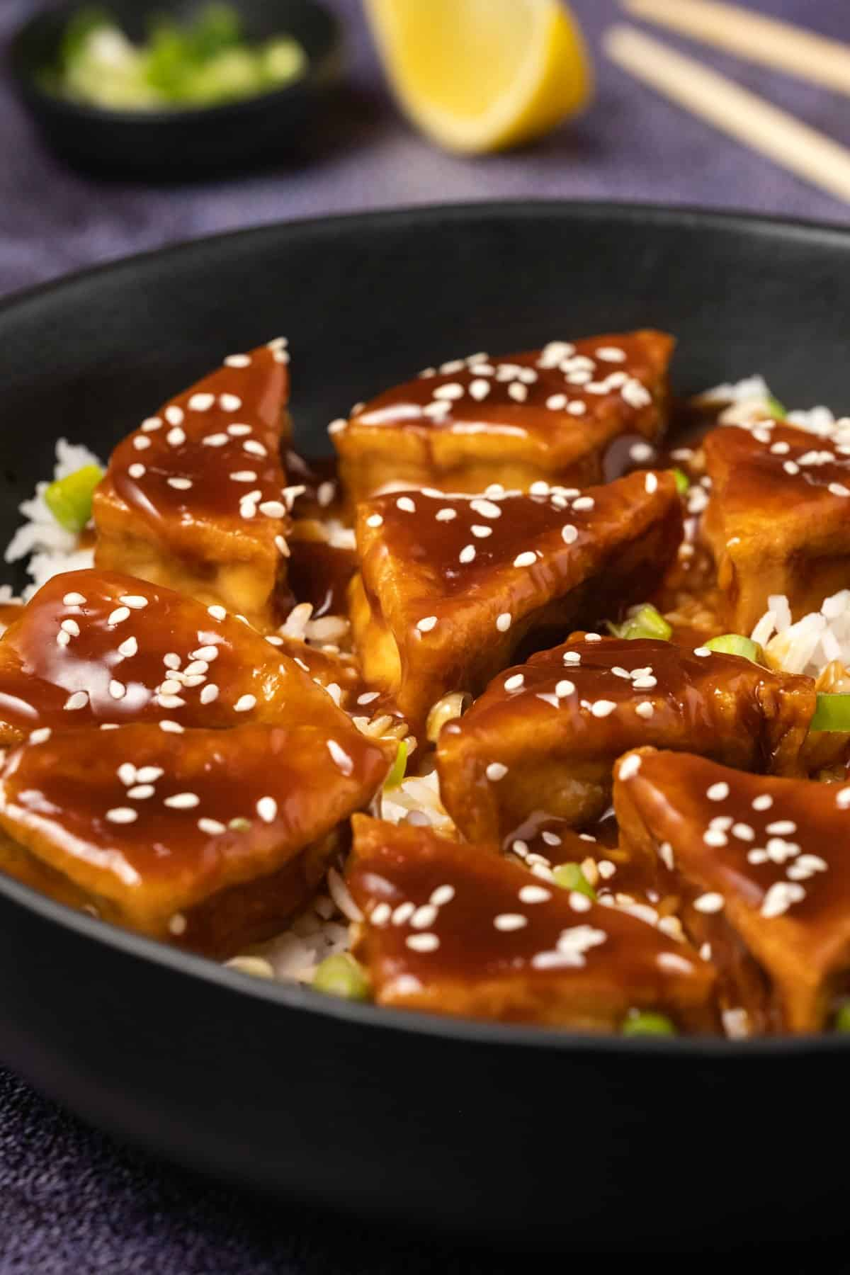 Teriyaki tofu with rice and sesame seeds in a black bowl.