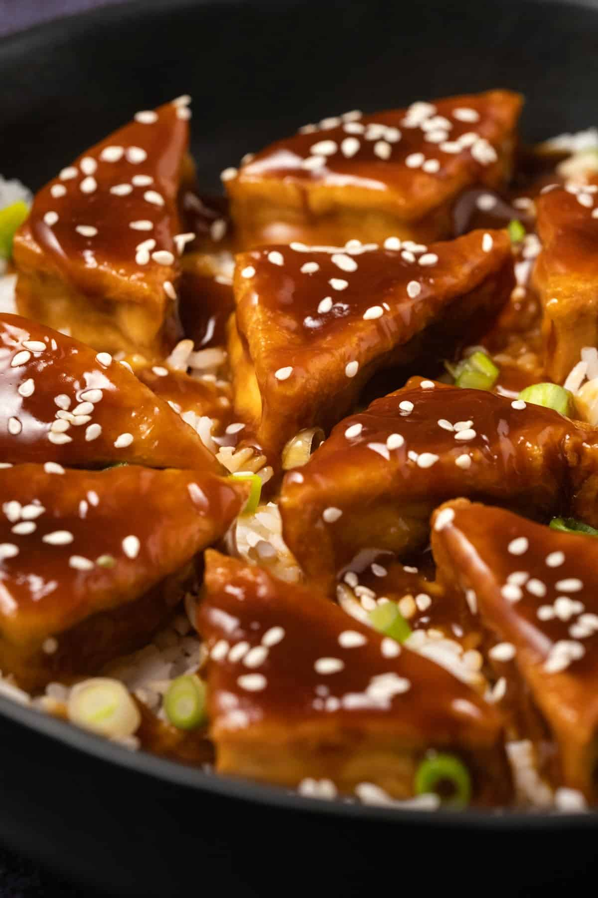 Teriyaki tofu in a black bowl with rice and sesame seeds.