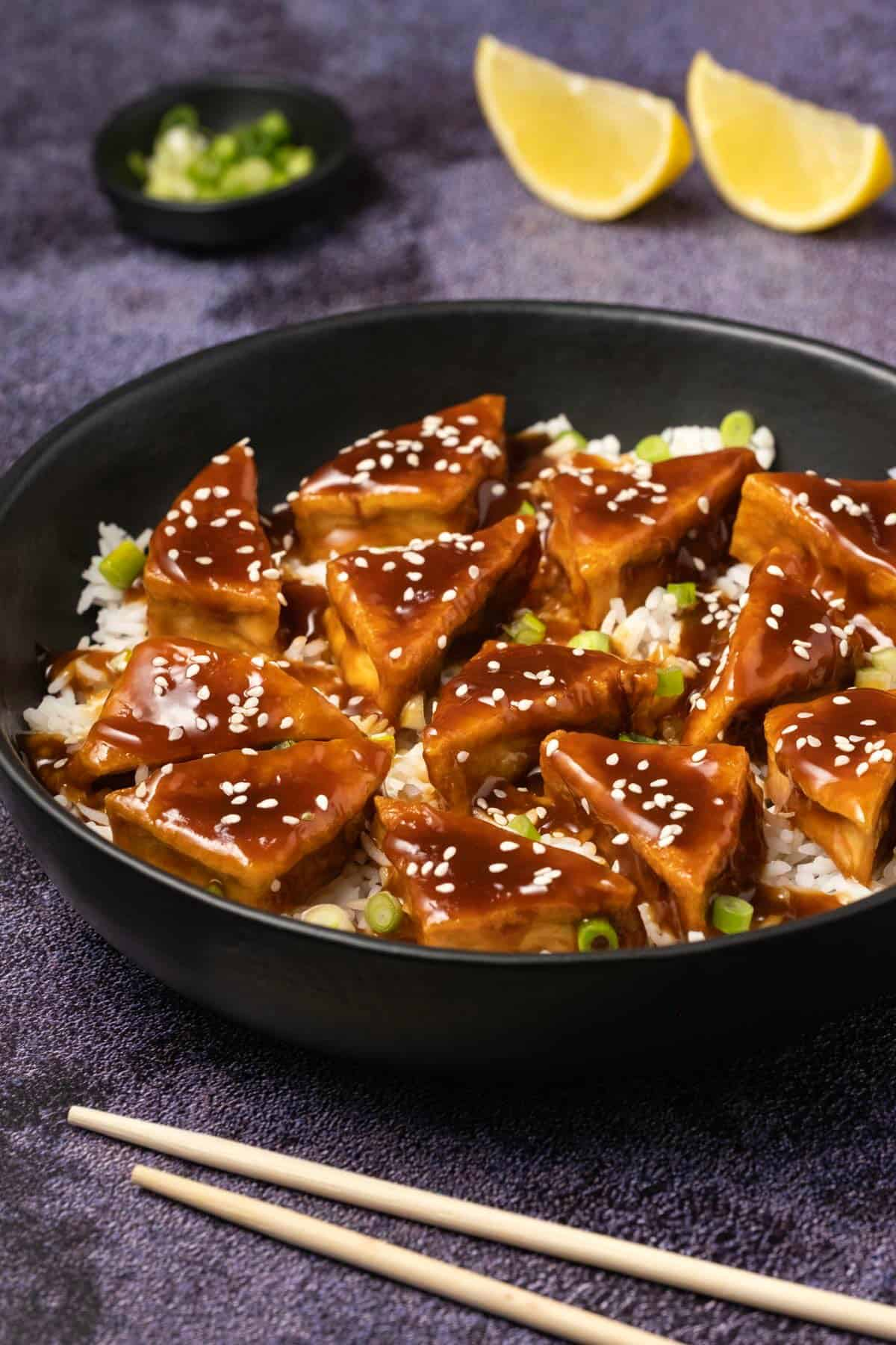 Teriyaki tofu with sesame seeds and rice in a black bowl.