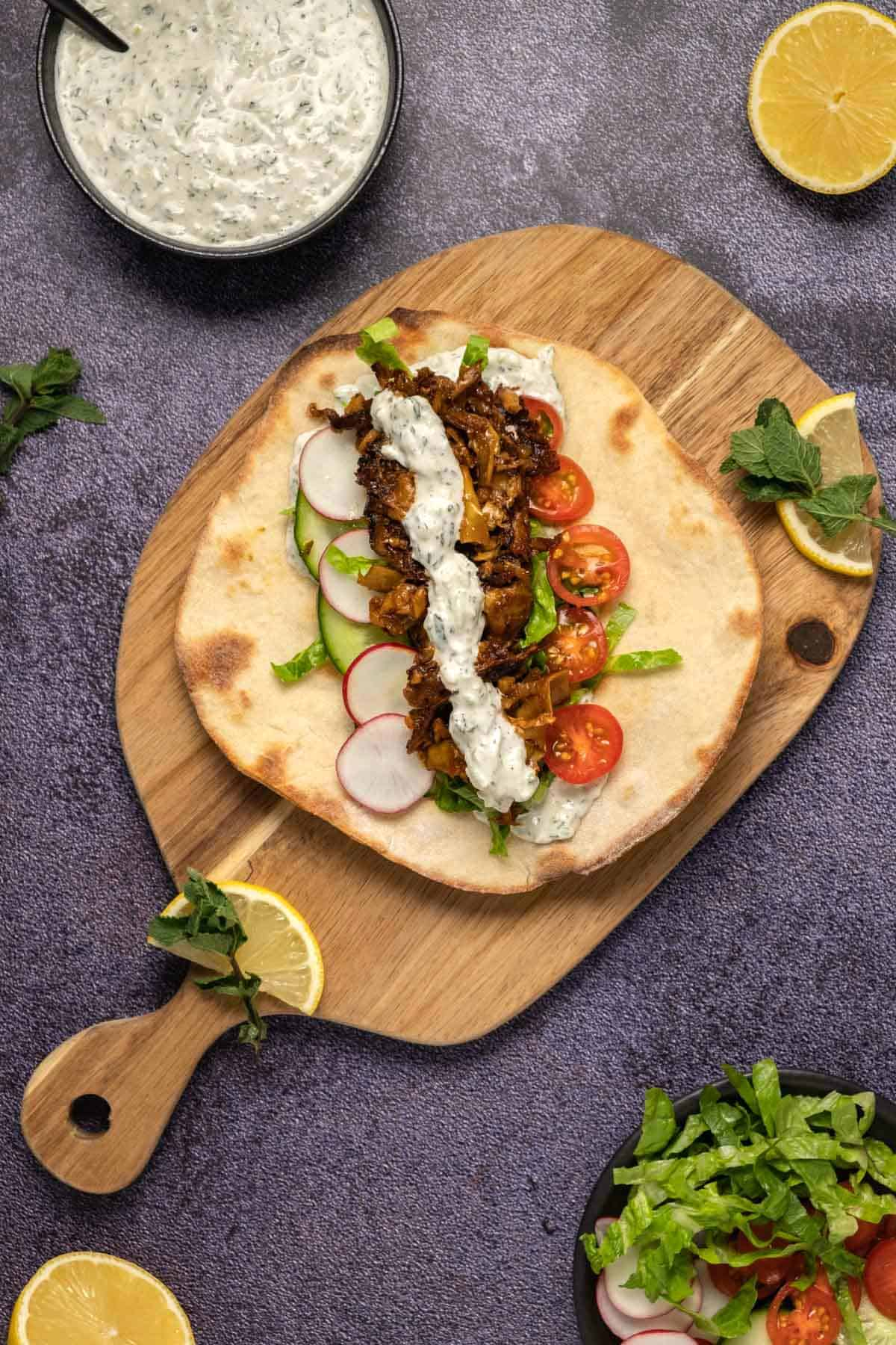 Pita bread topped with fillings and tzatziki on a wooden board.