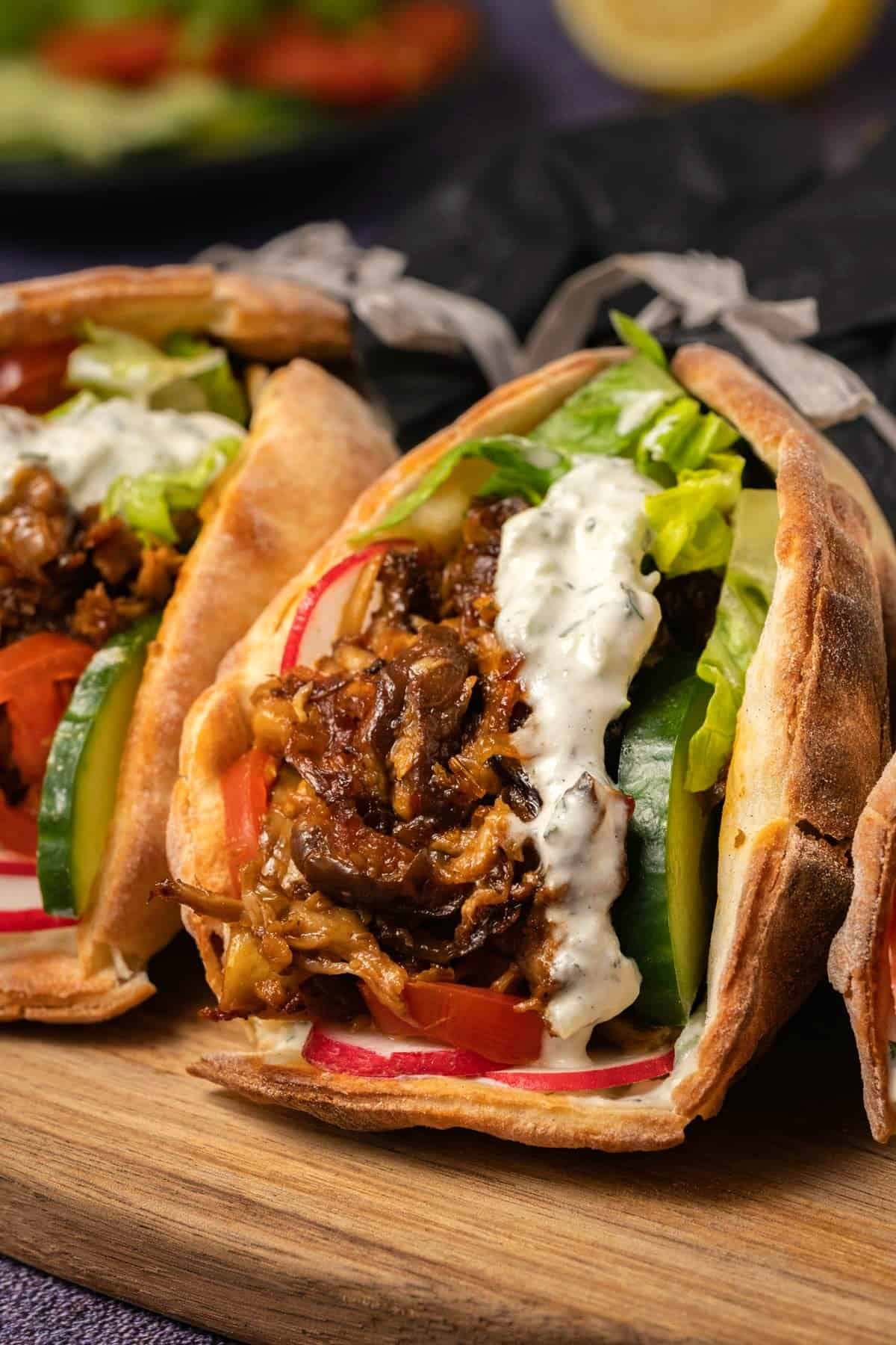 Vegan gyros with tzatziki on a wooden board.