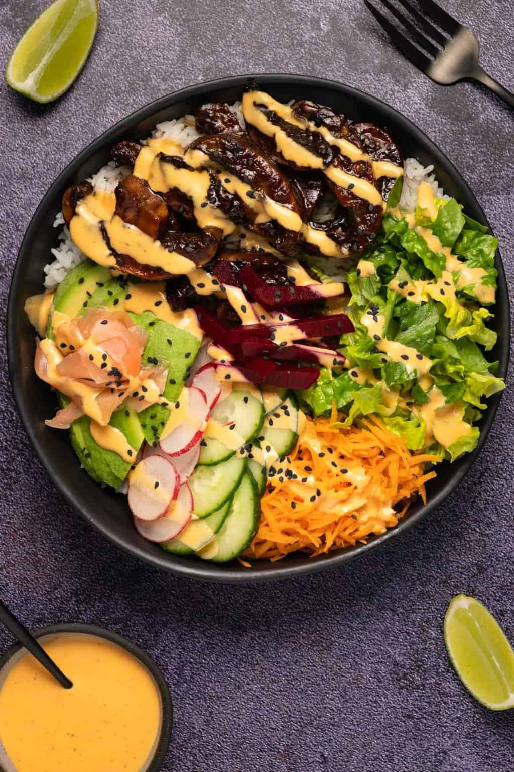 Black bowl filled with rice, salad and veggies and a drizzled dressing.