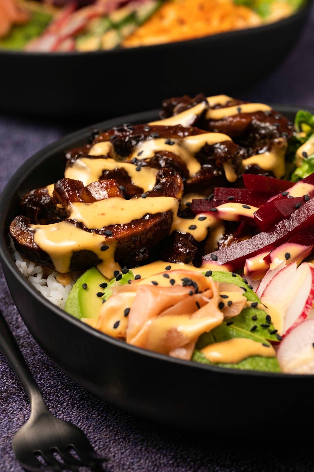 Black bowl with veggies, rice and salad.