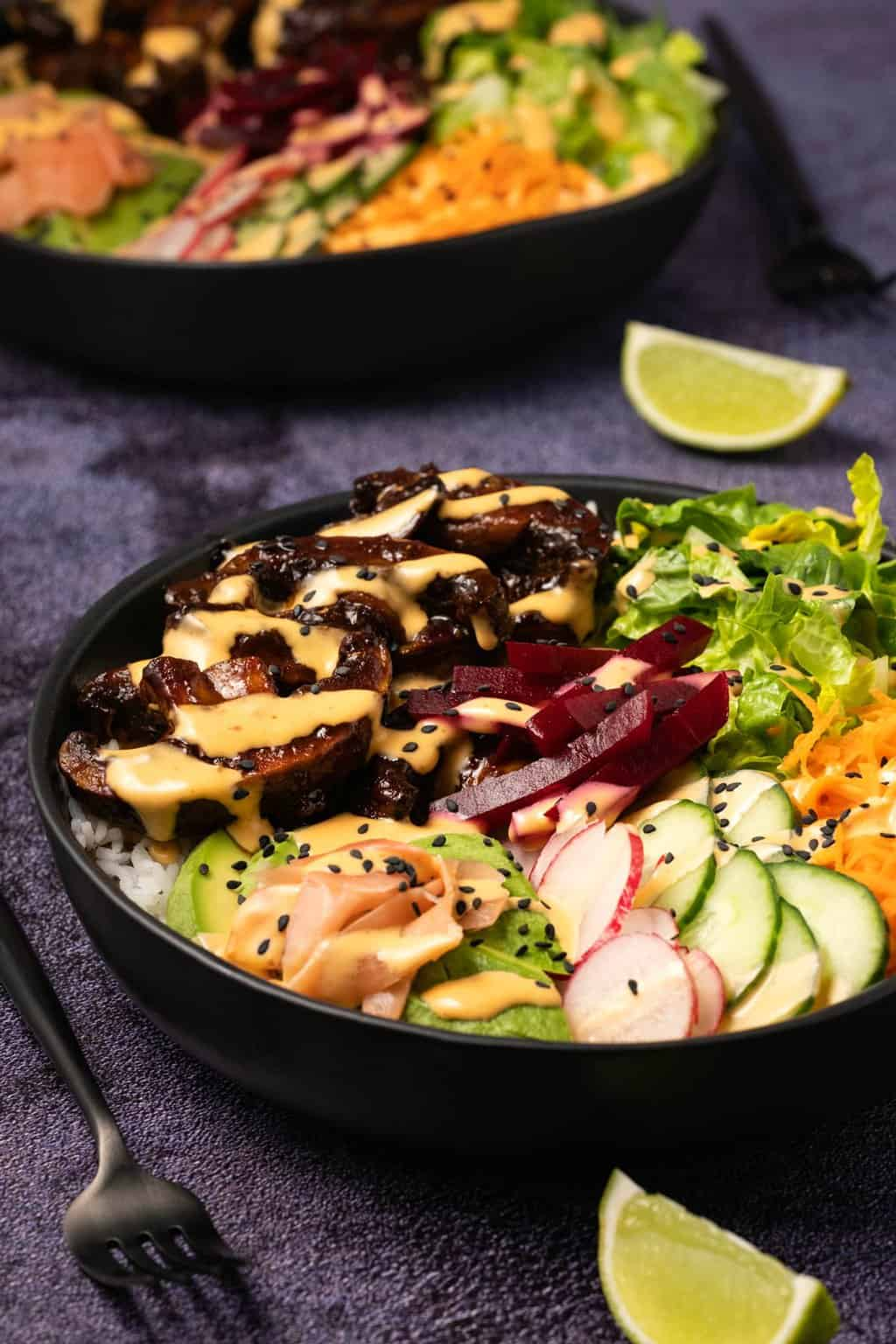 Black bowl with salad and rice and mushrooms, drizzled with a creamy dressing.