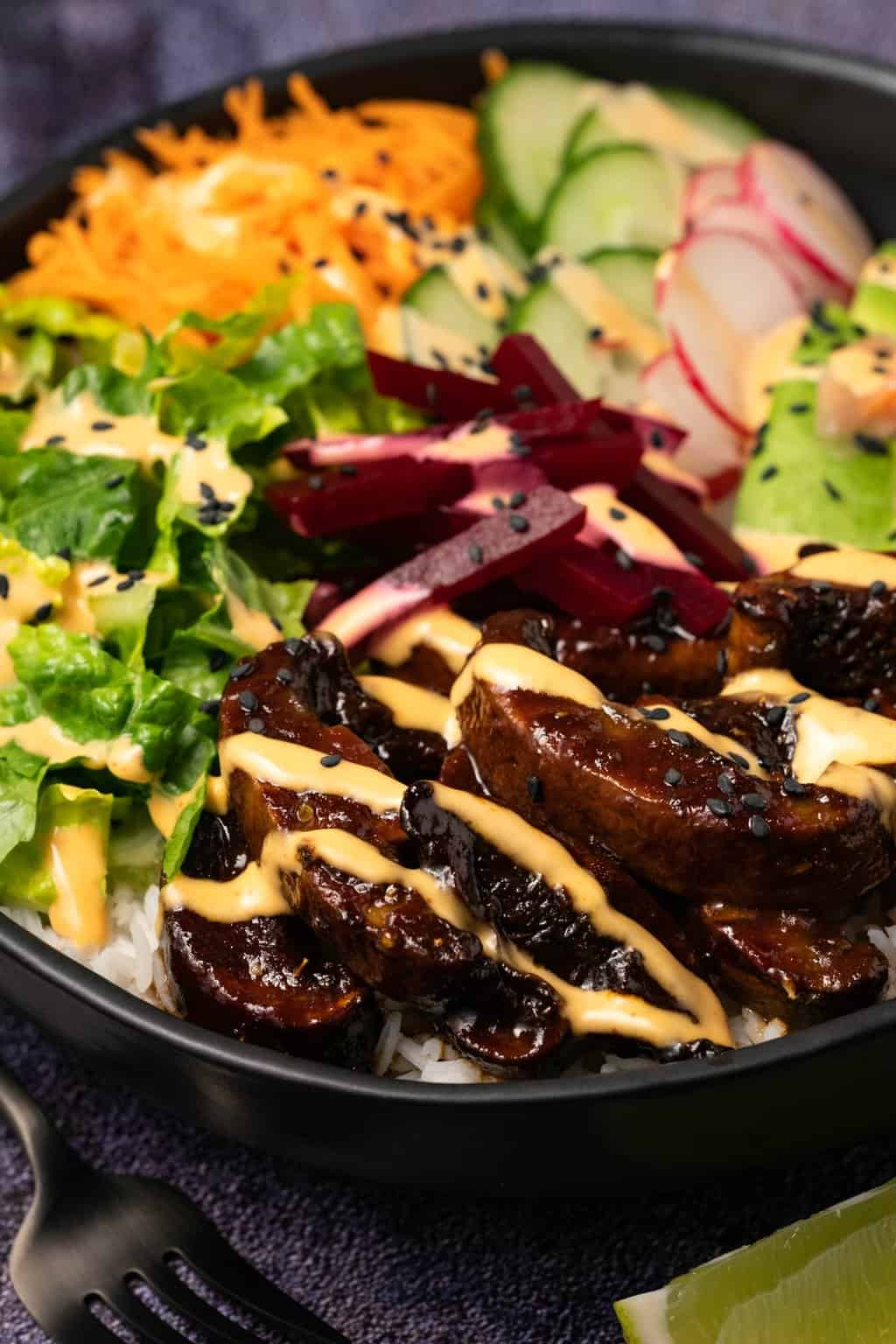 Black bowl filled with mushrooms, salad veggies and rice and drizzled with a creamy dressing.