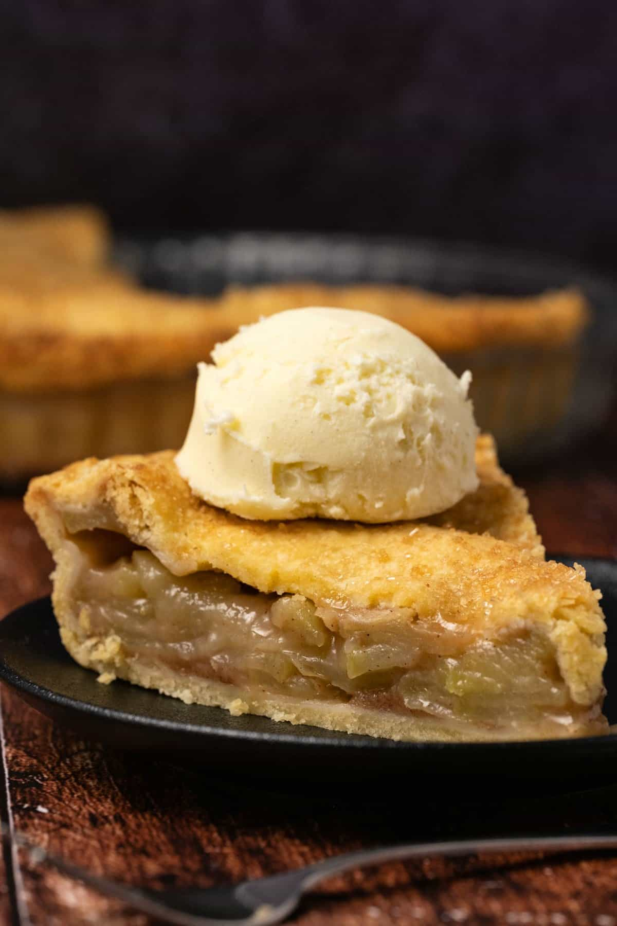 Slice of vegan apple pie topped with a scoop of ice cream on a black plate.