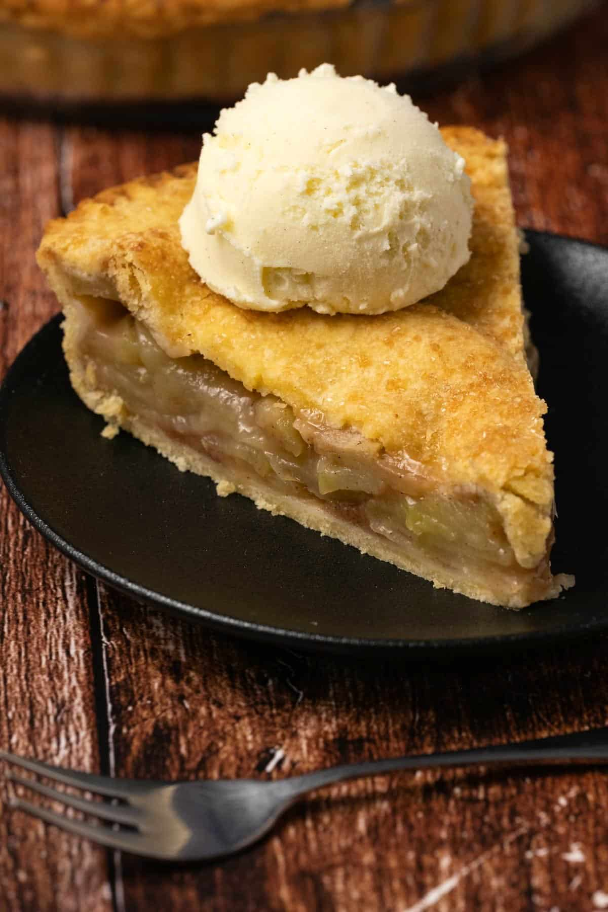 Slice of apple pie topped with ice cream on a black plate.
