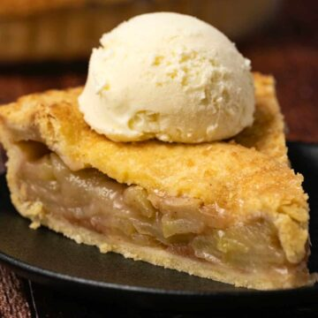 Slice of vegan apple pie topped with ice cream on a black plate.