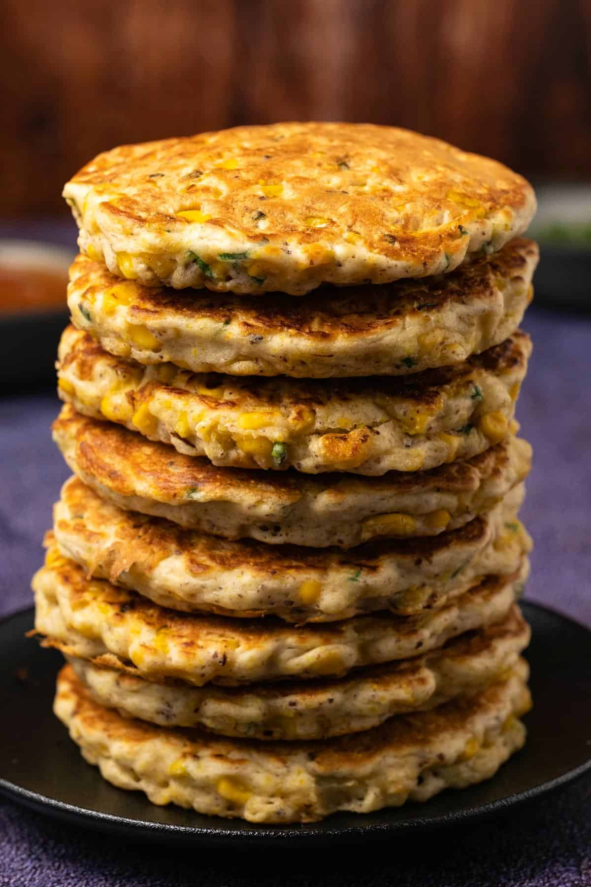 Stack of corn fritters on a black plate.