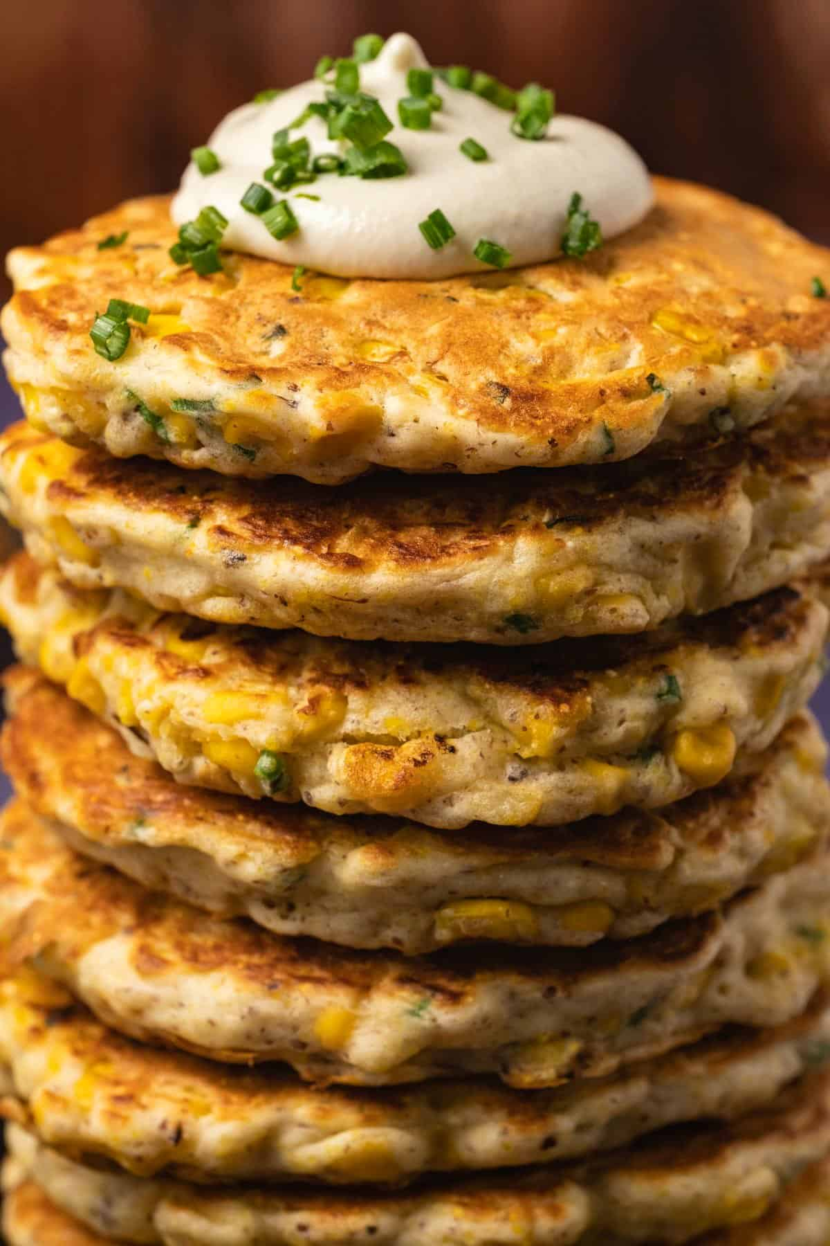 Stack of vegan corn fritters topped with sour cream and chopped chives.