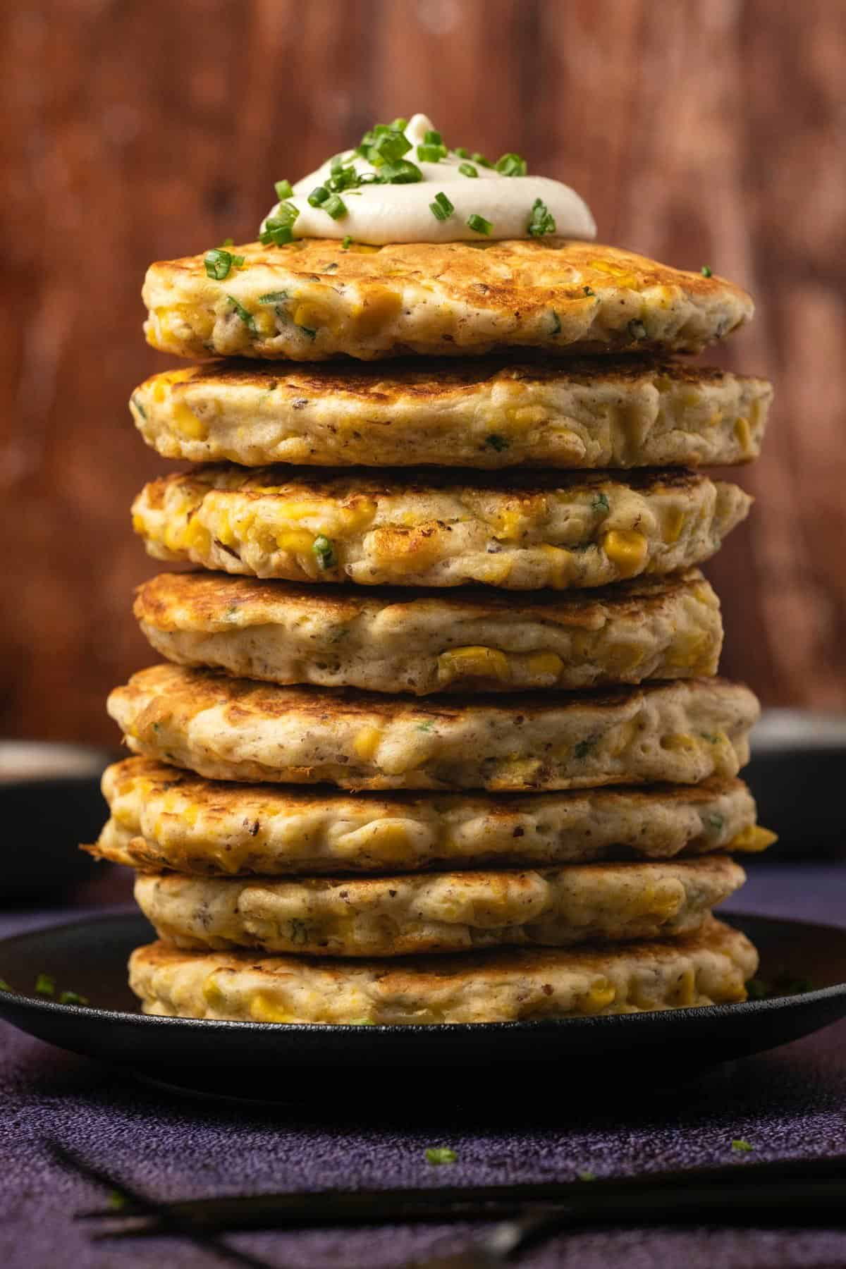 Stack of vegan corn fritters topped with sour cream and chives on a black plate.