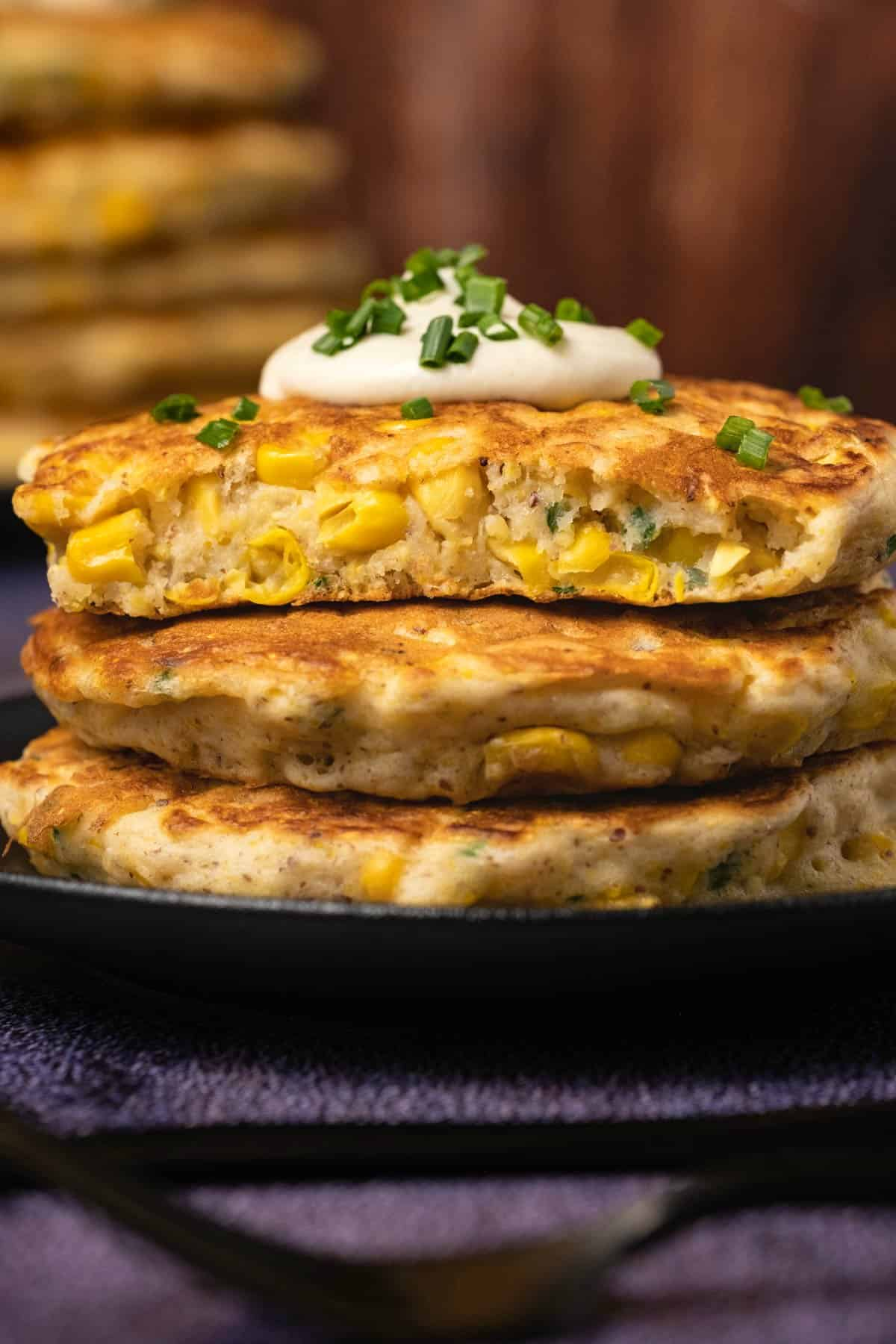 Stack of corn fritters on a black plate, the top fritter cut in half to show the center.