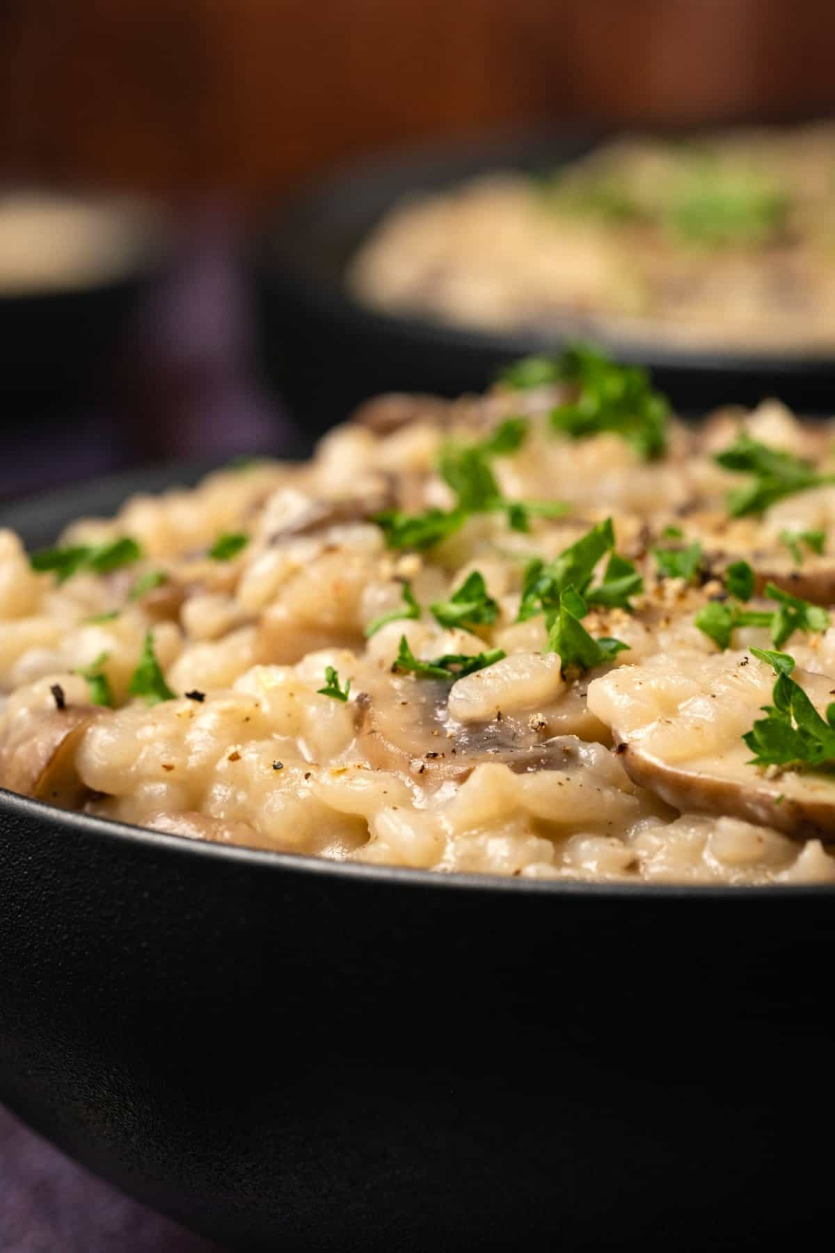 Vegan mushroom risotto in a black bowl with fresh parsley and ground black pepper.