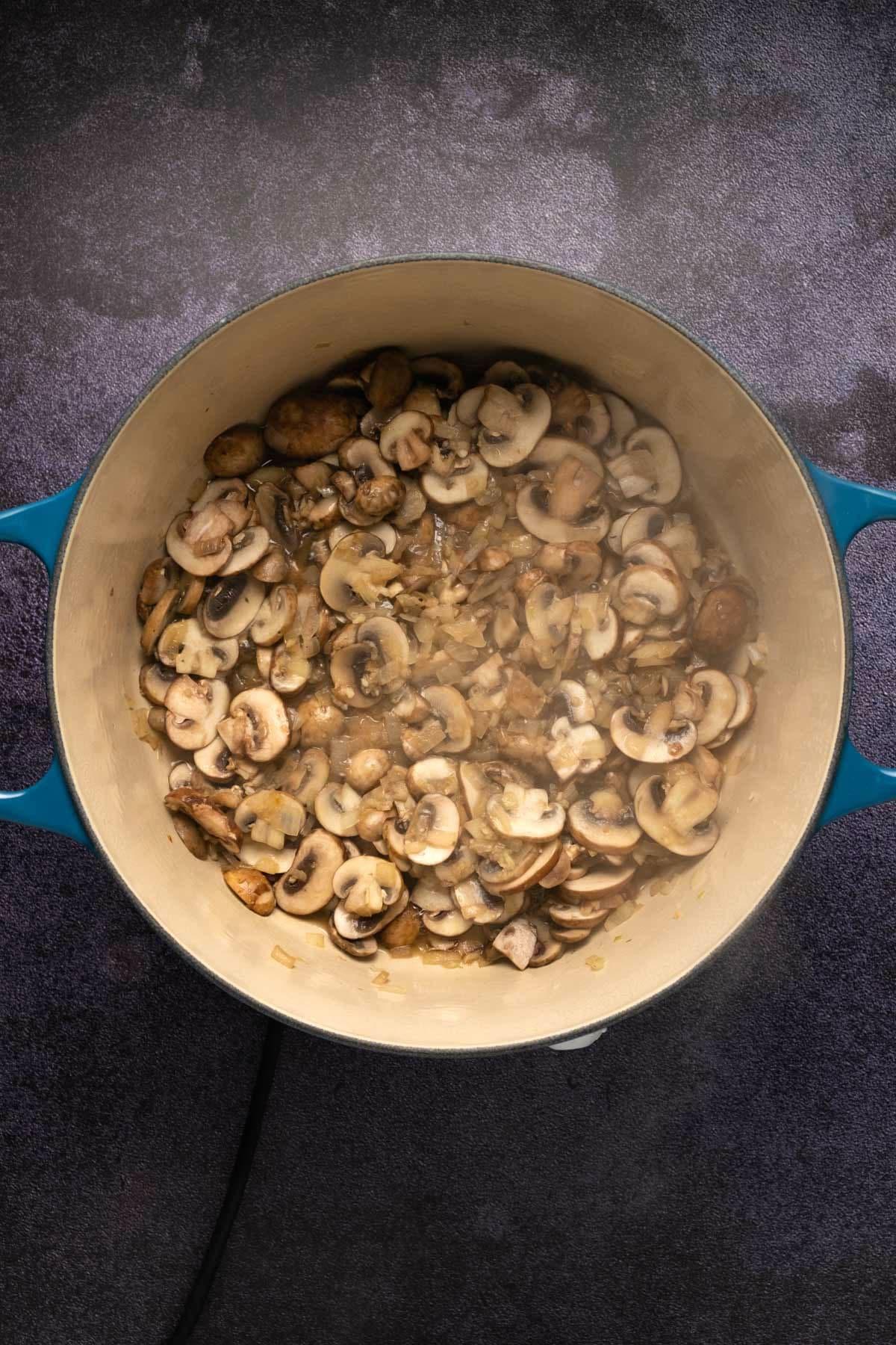 Sautéed mushrooms and onions in a pot.