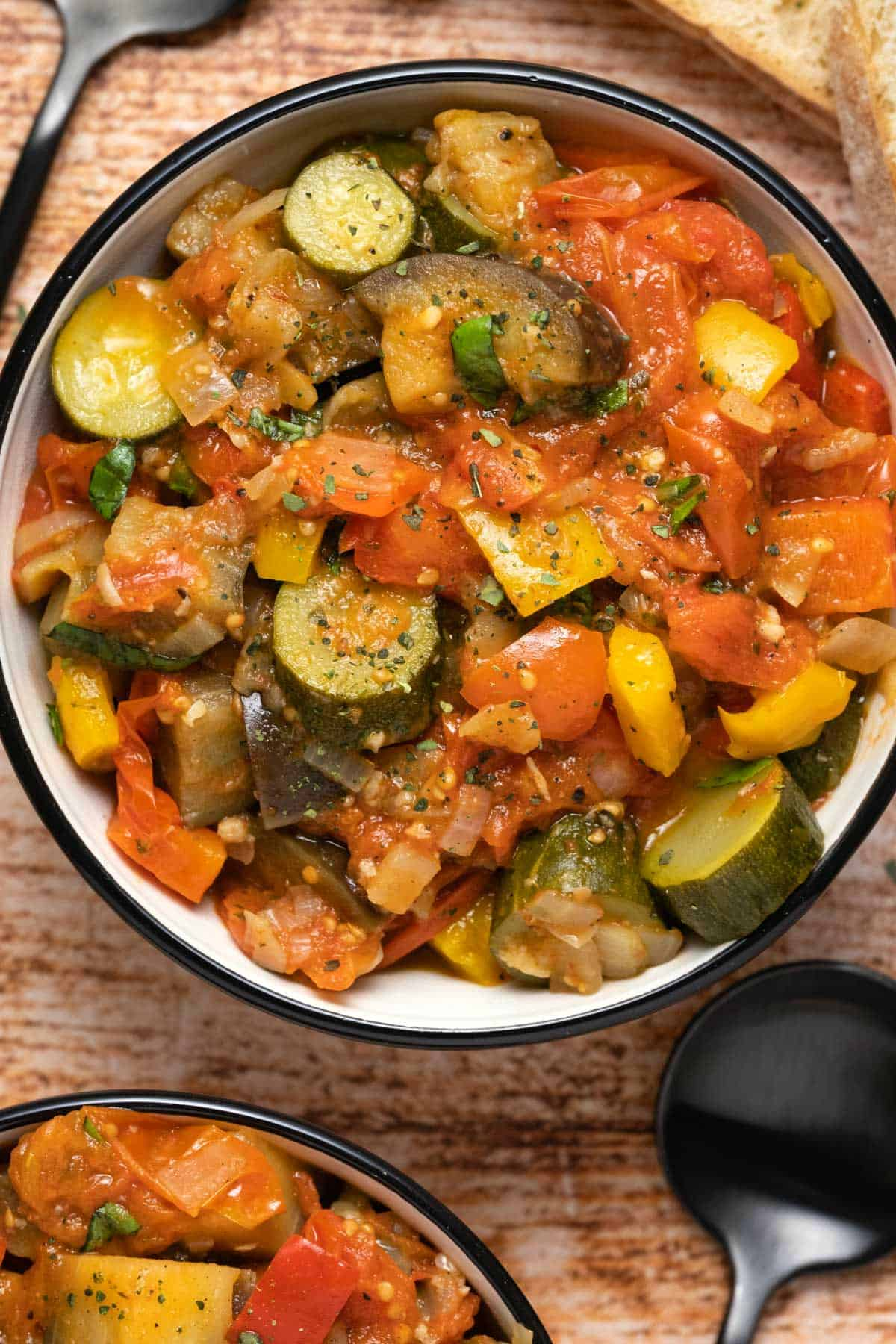 Ratatouille topped with black pepper and dried oregano in a ceramic bowl.