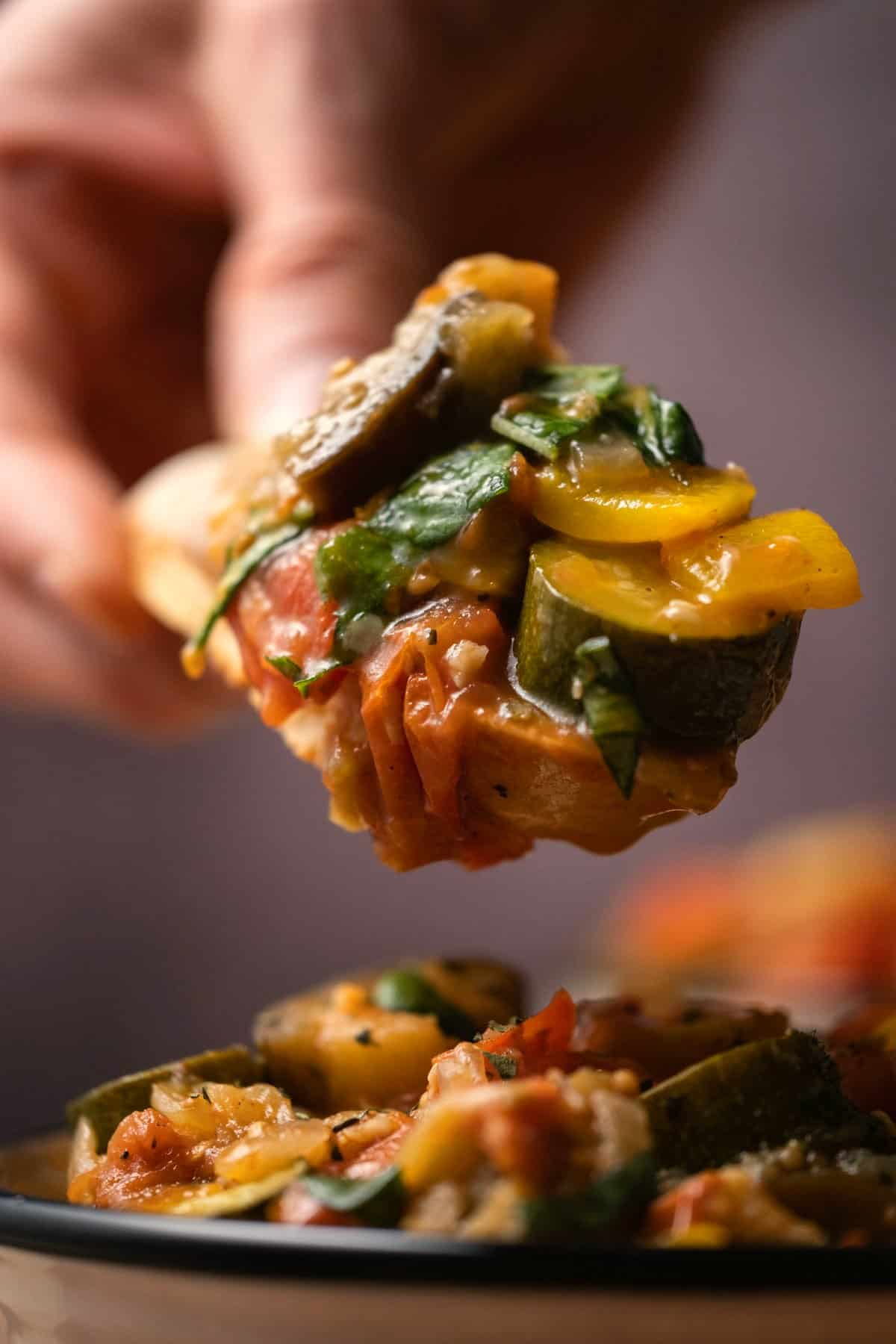 Ratatouille piled up on a slice of toasted baguette.