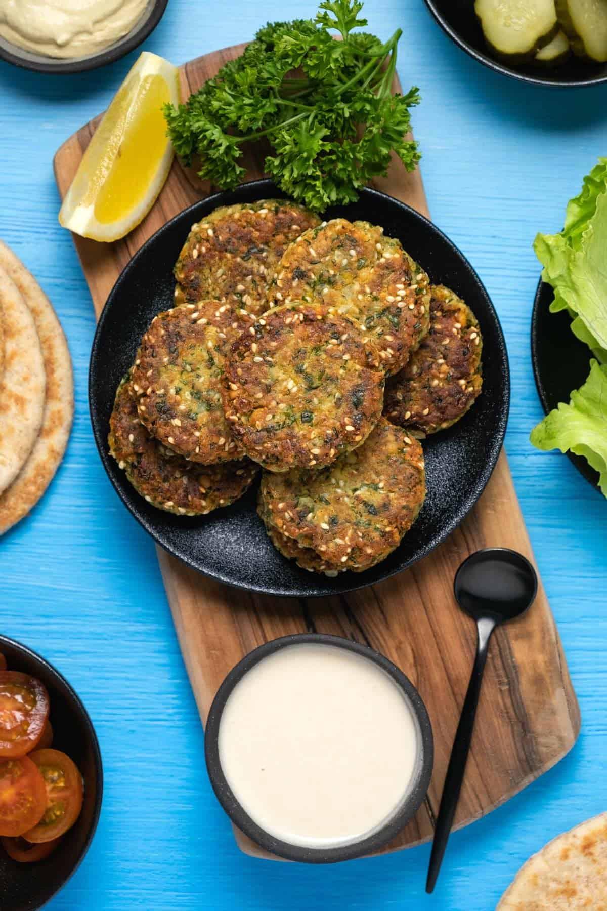 Vegan falafel stacked up on a black plate.