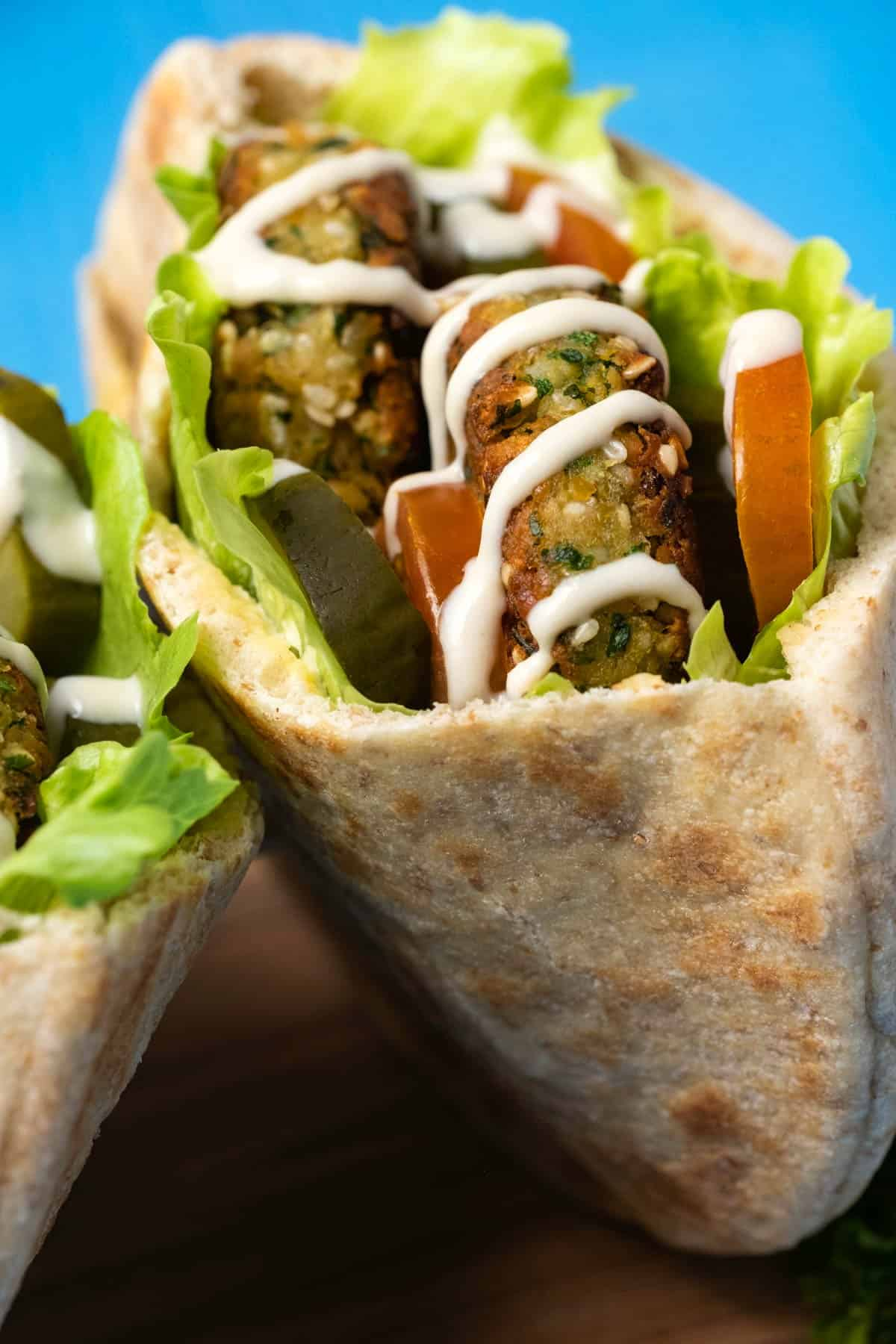 Falafel in pita breads with salad and tahini sauce.
