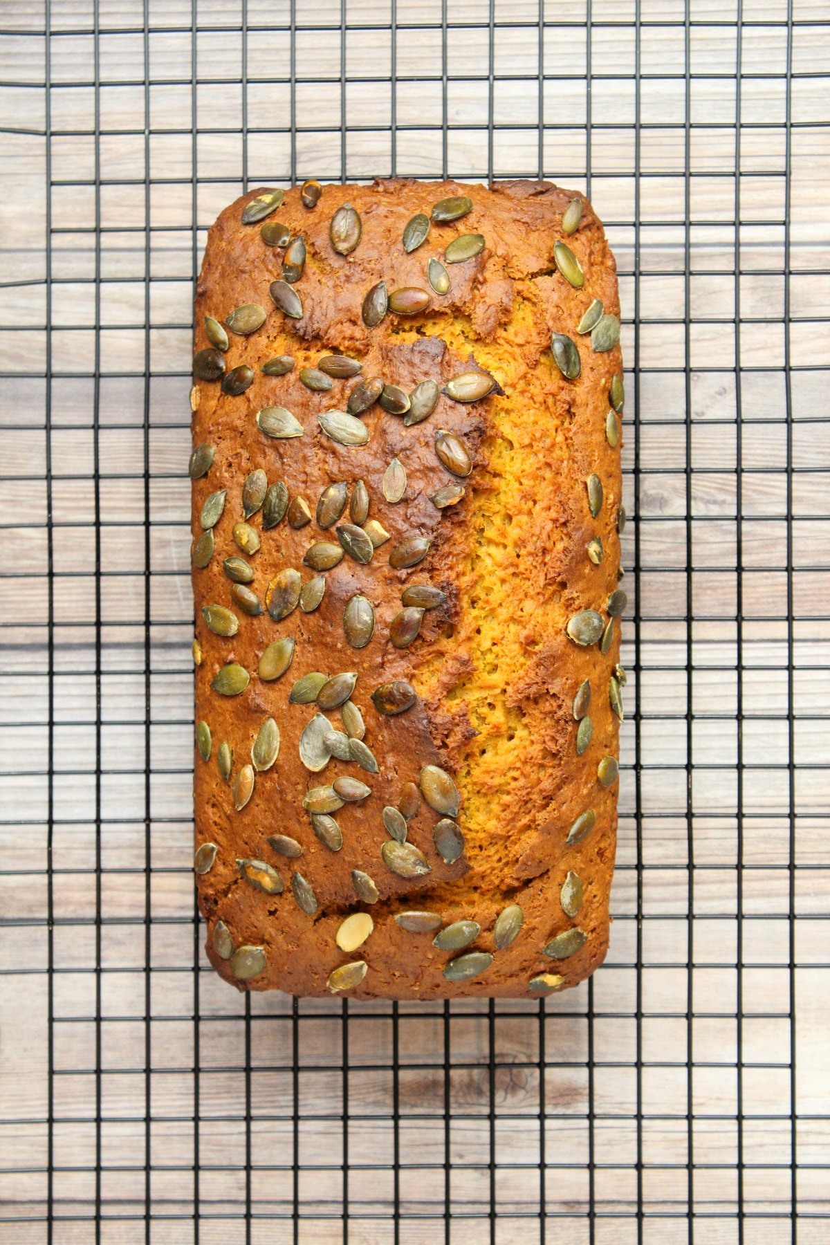Loaf of vegan pumpkin bread on a wire cooling rack.