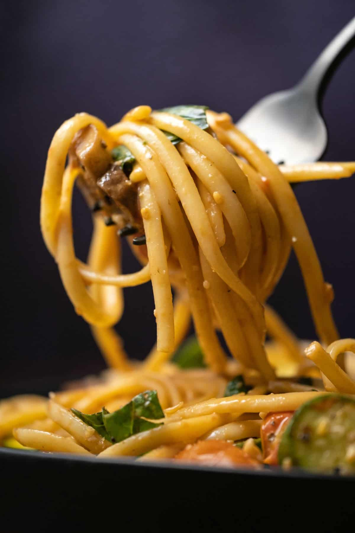 Linguine and vegetables on a fork.
