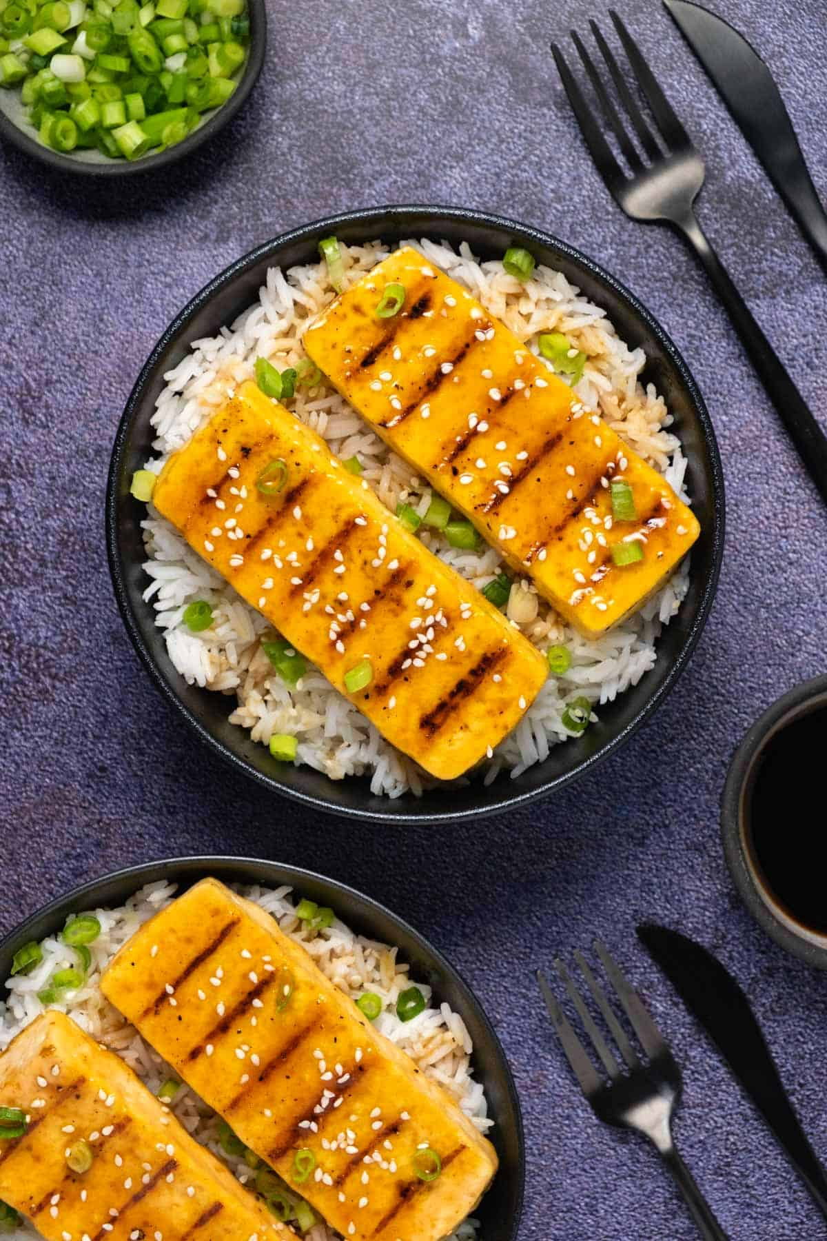 Grilled tofu served with rice and chopped green onions in a black bowl.