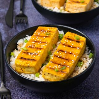 Grilled tofu with rice in black bowls.