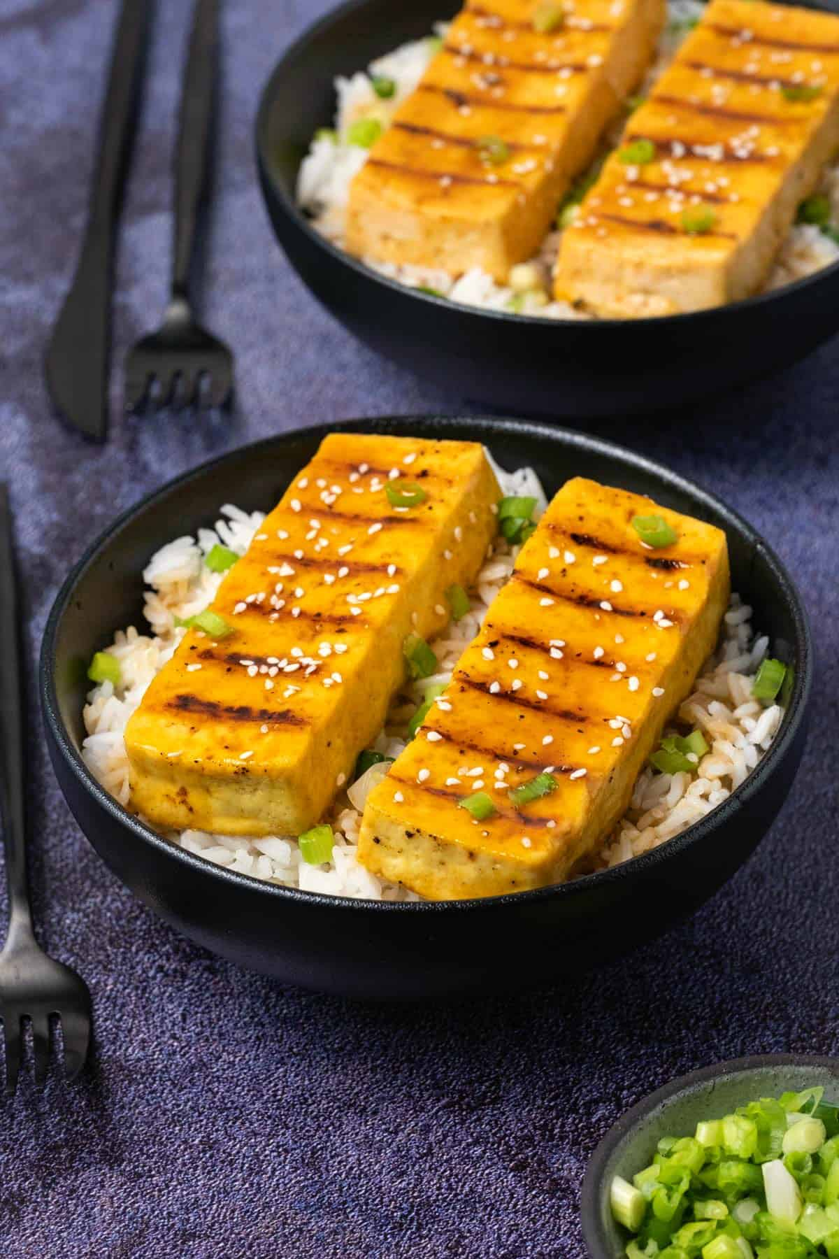 Grilled tofu with green onions and basmati rice in a black bowl.