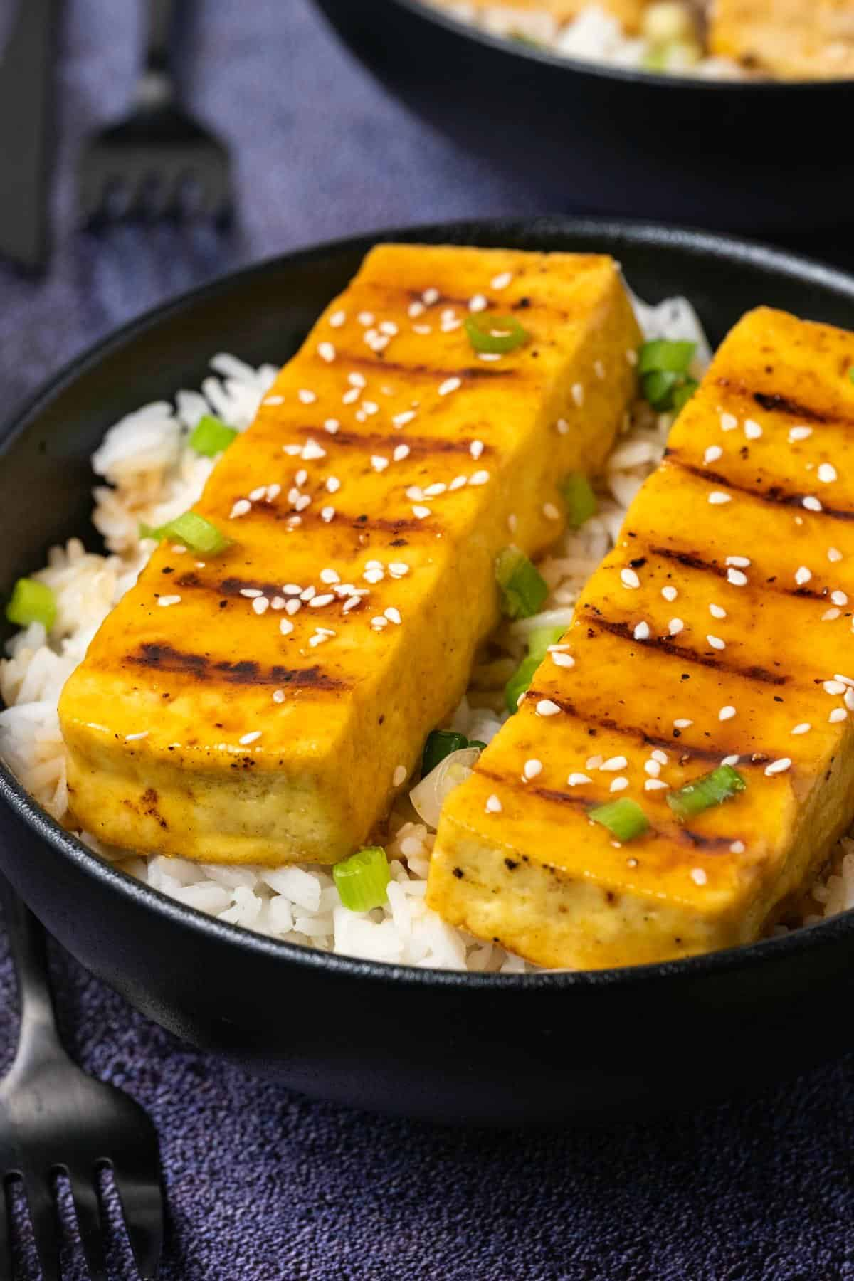 Grilled tofu with rice and green onions in a black bowl.