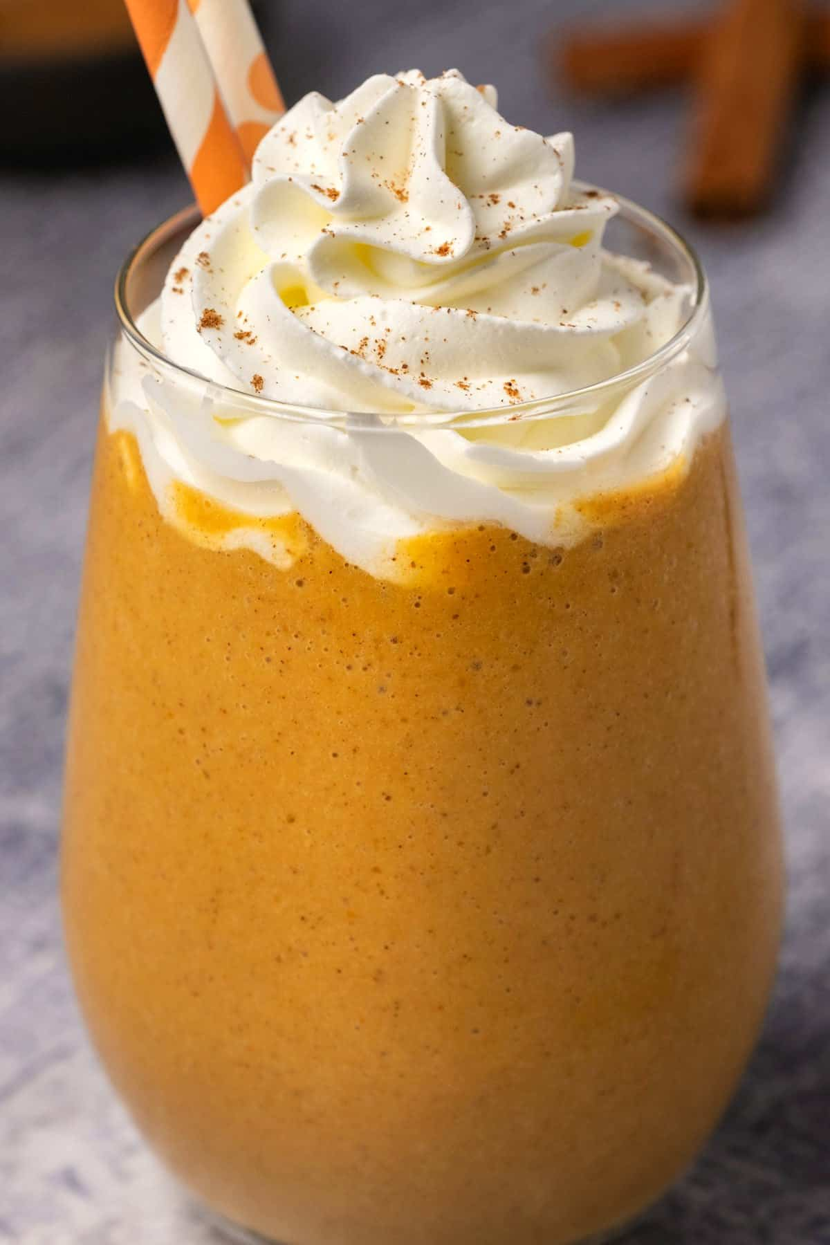 Pumpkin smoothie topped with whipped cream in a glass with two orange and white straws.