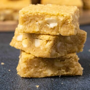 Vegan blondies stacked up in a stack of three.
