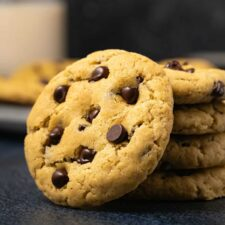 Vegan chocolate chip cookie leaning against a stack of cookies.