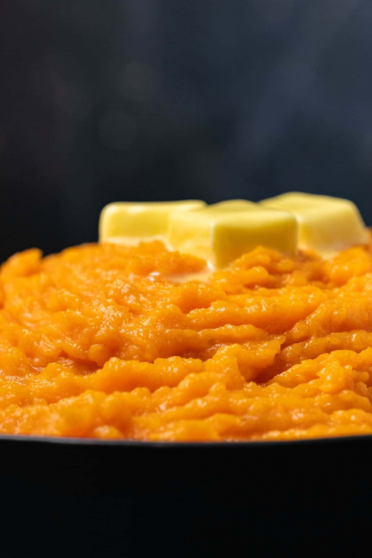 Vegan mashed sweet potatoes topped with butter in a black serving dish.