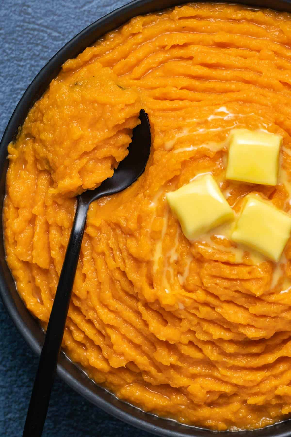 Vegan mashed sweet potatoes in a black bowl with a spoon.
