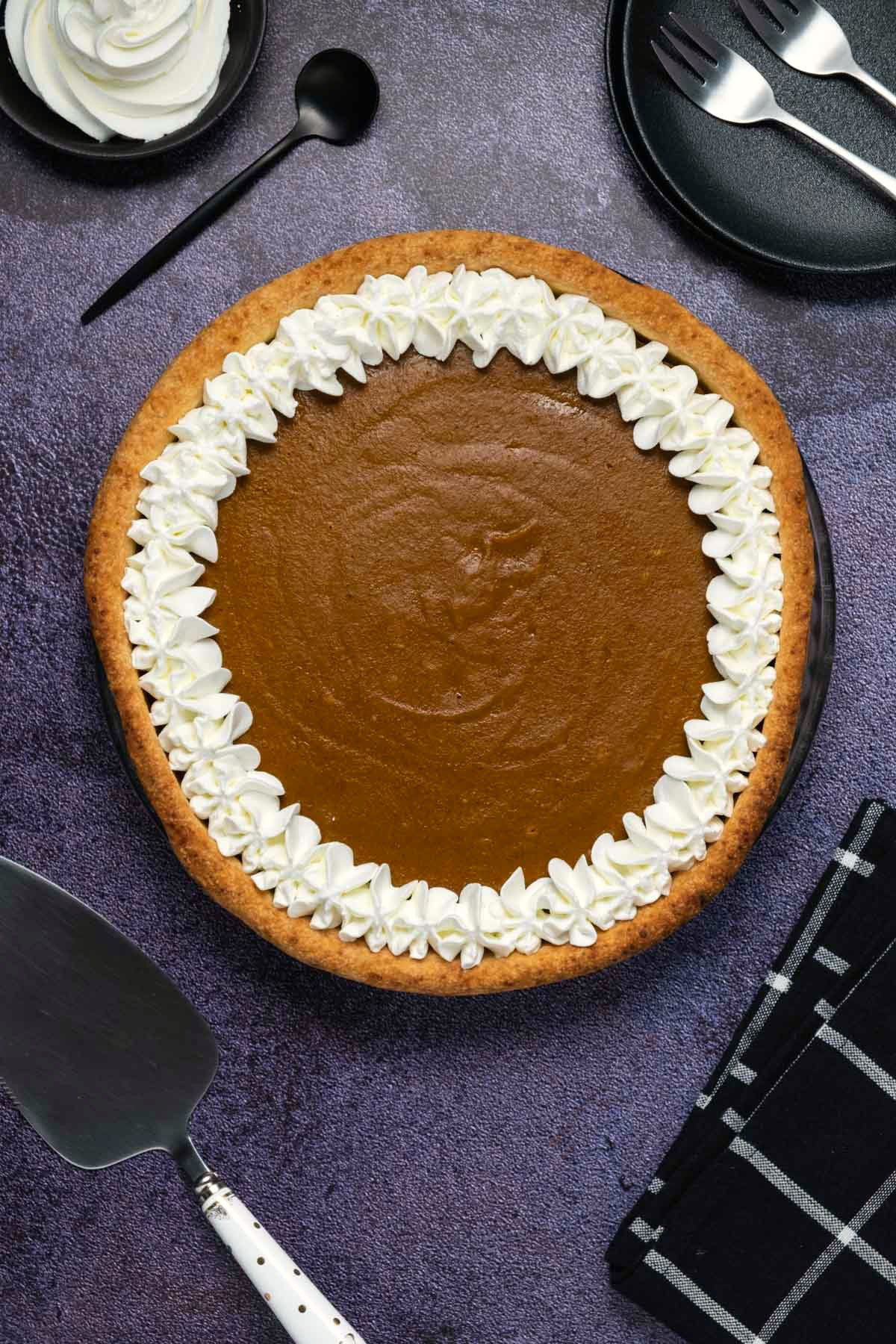 Pumpkin pie with whipped cream decoration in a glass pie dish.