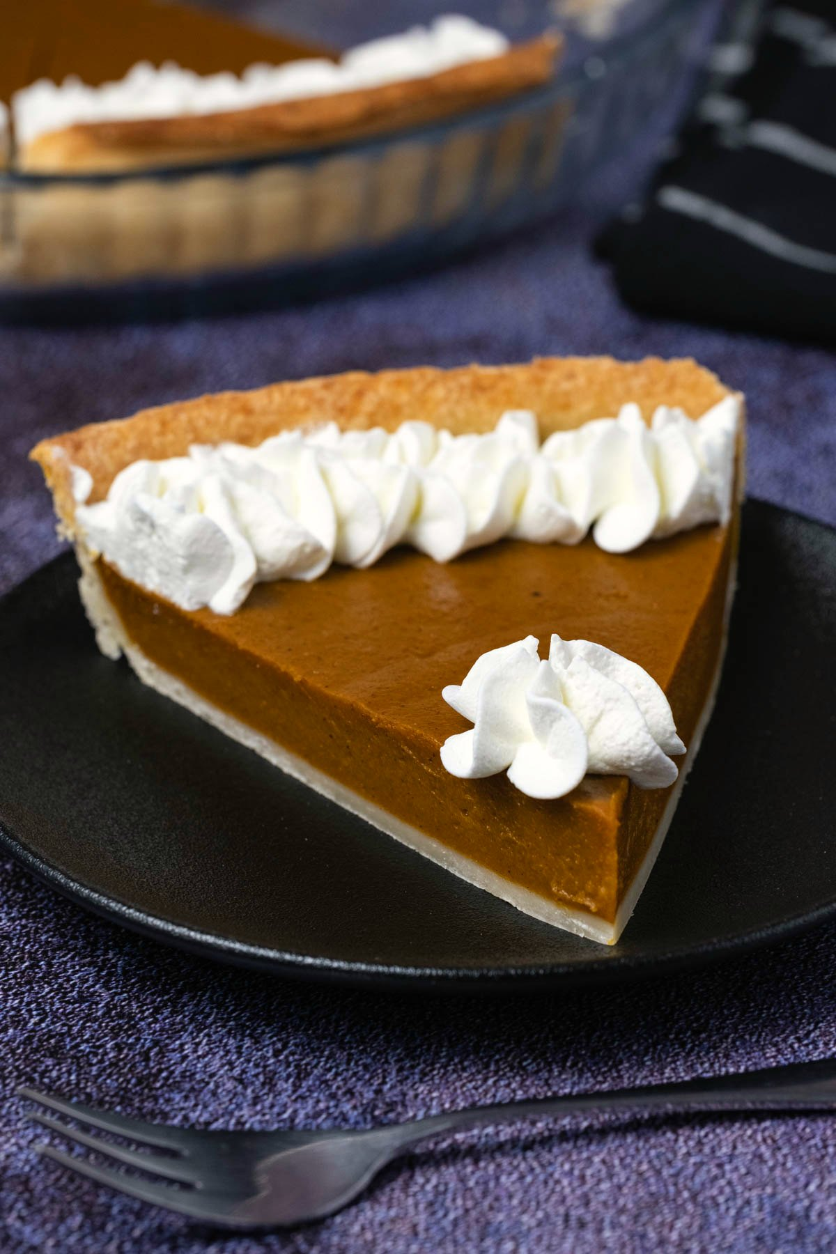 Slice of pumpkin pie with whipped cream on a black plate.