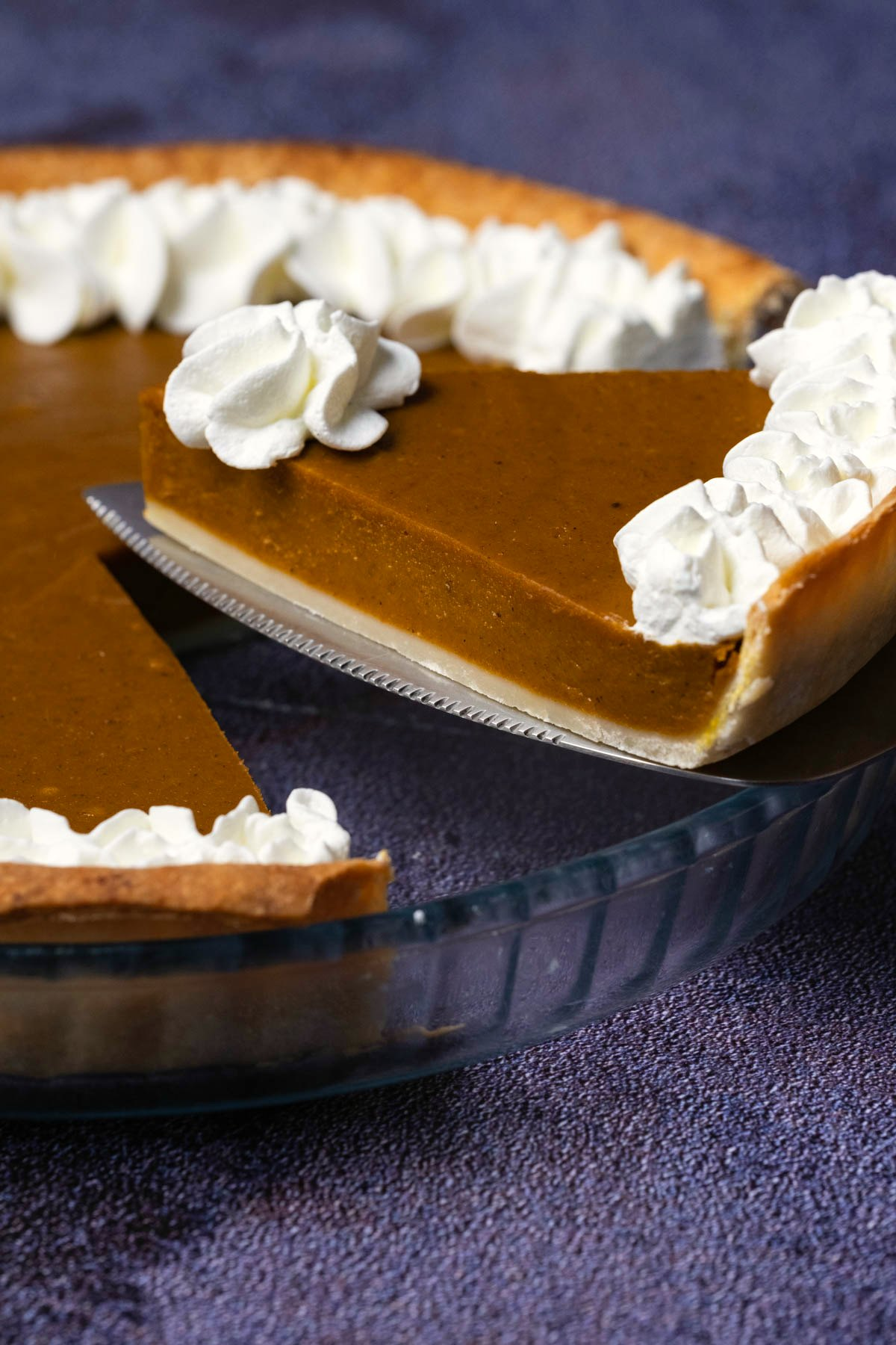 A slice of pumpkin pie lifting out of a pie dish.