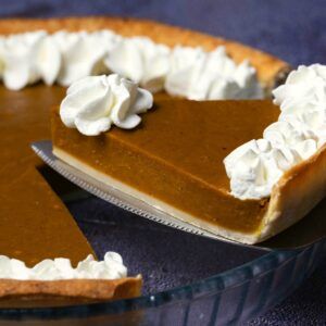 Vegan pumpkin pie in a glass pie dish with one slice cut and ready to serve.