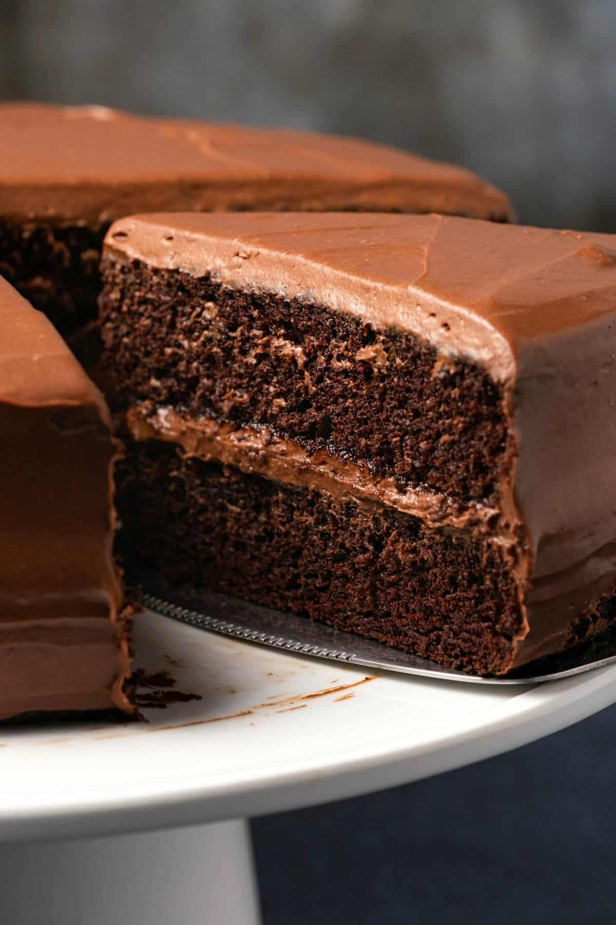 Chocolate cake on a white cake stand with one slice cut and ready to serve.