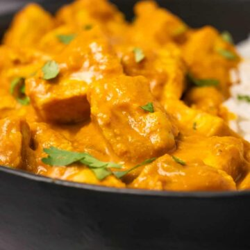 Vegan butter chicken with rice in a black bowl.