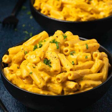 Vegan butternut squash mac and cheese in black bowls.