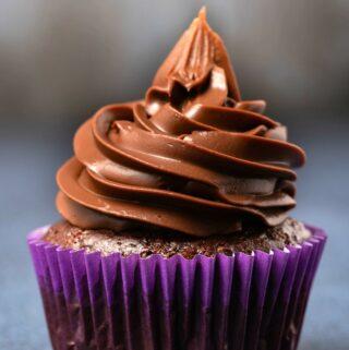 Vegan chocolate ganache piped onto a cupcake