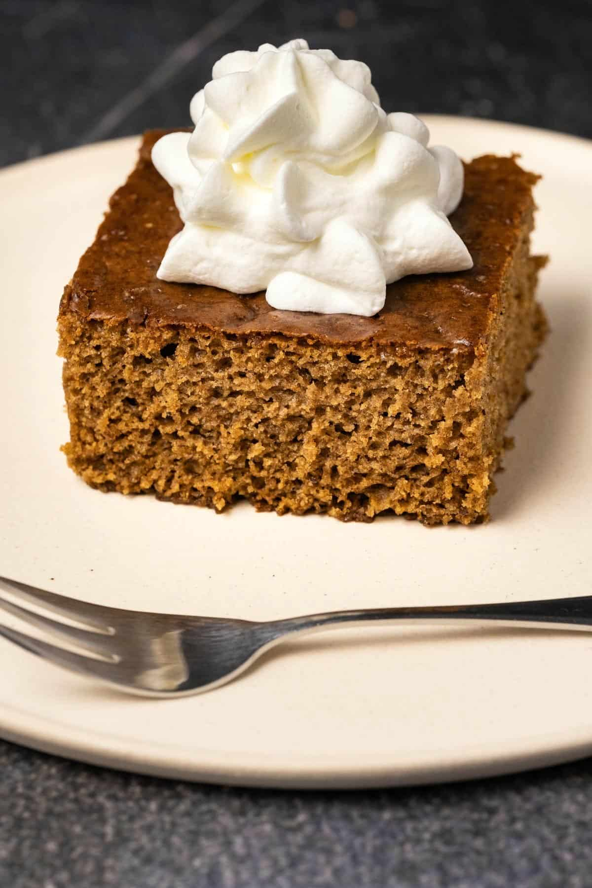 Slice of gingerbread cake with whipped cream, on a white plate with a cake fork.