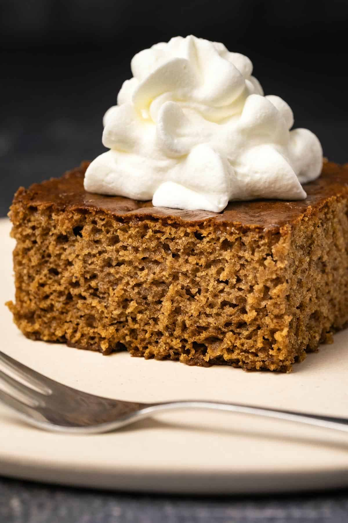 Slice of gingerbread with whipped cream on a white plate with a cake fork.