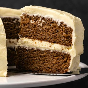 Vegan gingerbread cake with a slice cut and ready to serve on a white cake stand.