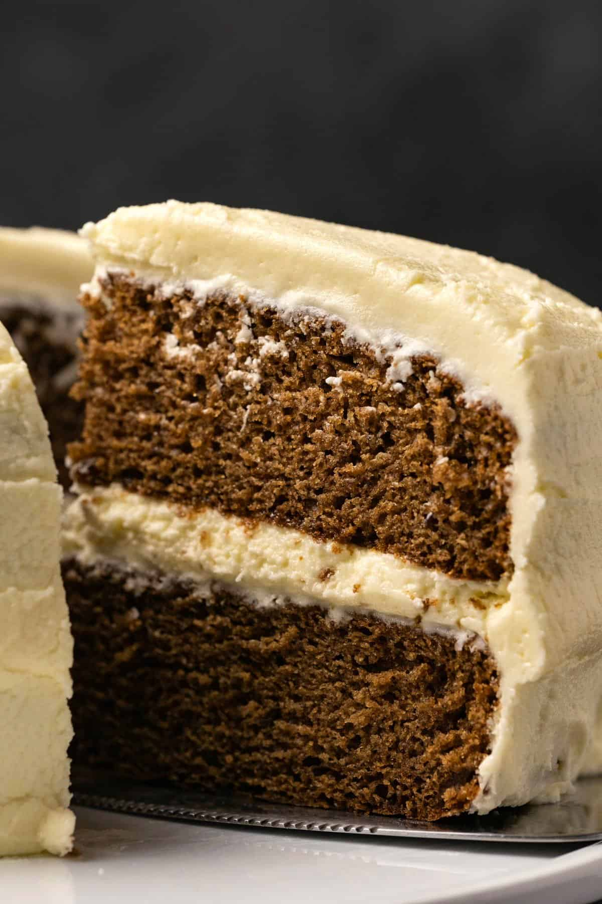 Vegan gingerbread cake on a white cake stand with one slice cut.