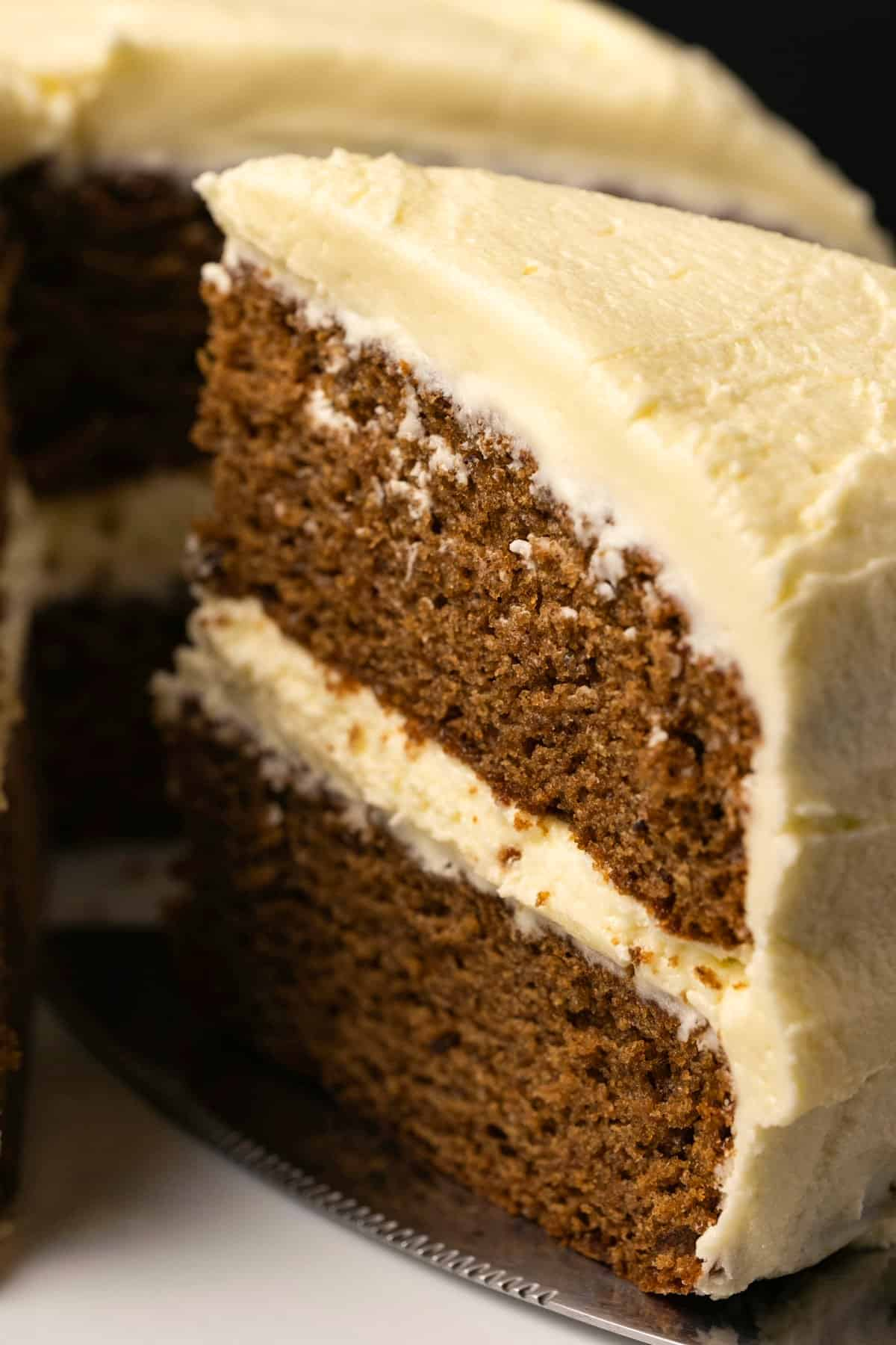 Vegan gingerbread cake on a white cake stand with one slice cut and ready to serve.